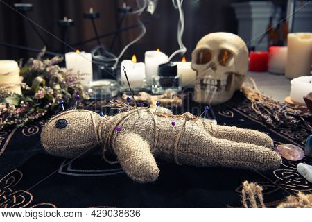 Voodoo Doll With Pins And Dried Flowers On Table Indoors