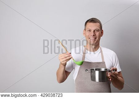 Happy Man With Cooking Pot And Ladle On Light Grey Background. Space For Text