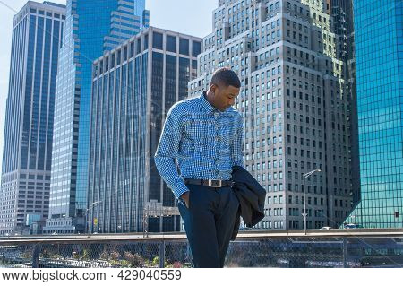 A Young Black Businessman Is Standing In A Business District, Looking Down And Into Deeply Thinking.