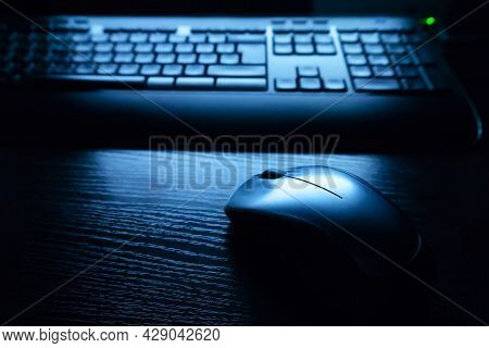 Keyboard And Mouse In The Light Of The Monitor. Dark Tones. Backlight