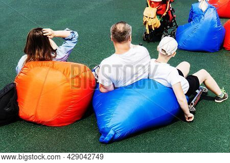Family Resting On A Bag-bob In A Recreation Area. Family Walks In The City. Summer Pastime.