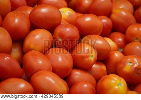 Bunches Of Ripe Red Tomatoes Laying In A Fruit Box Ready For Sale At Farmers Market. Tomato With Tai