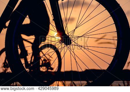 Close-up Silhouette Of A Bike Wheel At Sunset. The Sun Shines Through The Wheel Of A Bicycle With Bl
