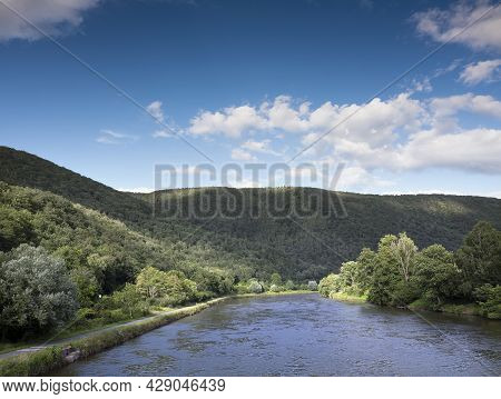 Dense Green Forest Around River Maas In French Ardennes Under Blue Sky In Summer