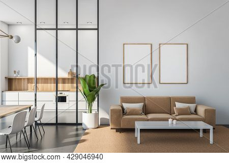 A Row Of Wood Framed Posters On A Grey Wall With The Seating Area Interior. Sofa And Coffee Table An
