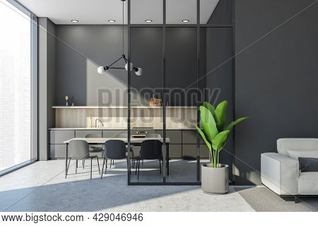 Panoramic Grey Kitchen Interior With A Simplified Cabinet Design, Table, Frame Chandelier And Glass