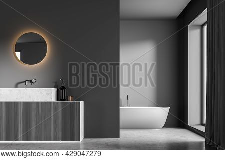 Illuminated Mirror And Vanity Next To A Dark Grey Partition Wall Of The Bathroom And An Oval Ceramic