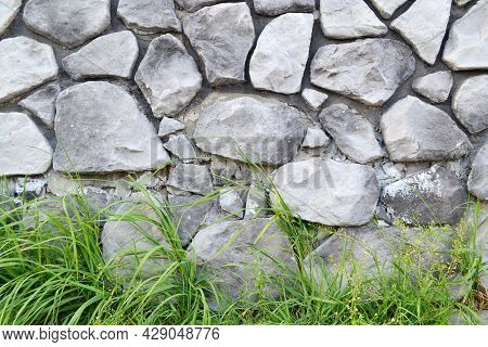 Black And White Background Of A Stone Wall, Green Grass At The Bottom.the Walls Are Made By Hand Fro