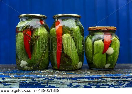 Pickled Pickled Cucumbers In Glass Jars On A Wooden Bench In The Hole Of A House In The Village. Blu