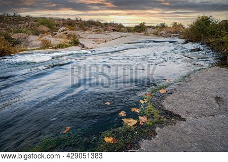 A Small Shining Stream Flows Among Smooth Wet And Dark Stones