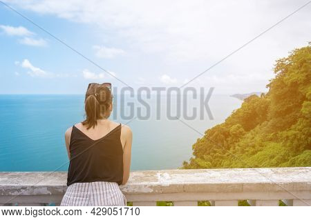 Young Caucasian Woman In Black Top Overlooking The Sea And Forest. Copy Space. Top View From Botanic