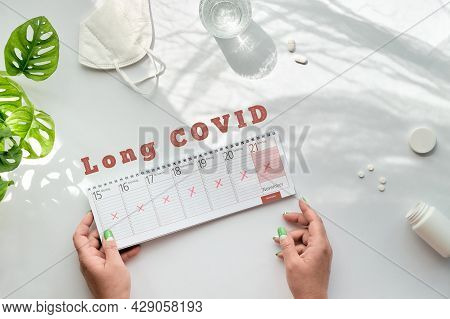 Text Long Covid, Patient Hands Hold Weekly Planner, Calendar With All Day Schedules Crossed Out. Can