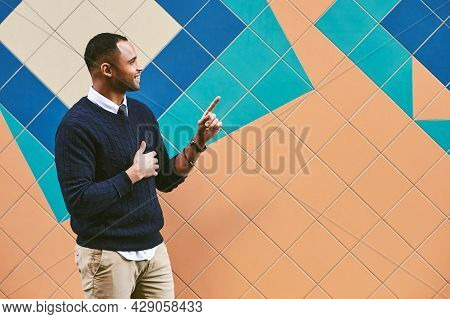 Outdoor Portrait Of Handsome African American Man, Wearing Blue Pullover, Pointing On The Side
