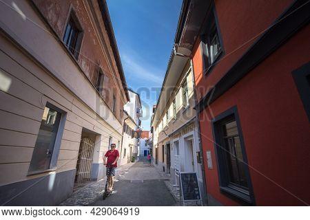 Kranj, Slovenia - June 15, 2021: Man Riding An Electric Scooter Driving In A Narrow Street Of Staro