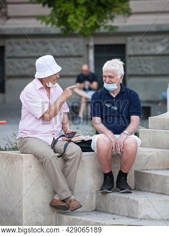 Belgrade, Serbia - July 22 2021: Old Men Friends, Sitting And Discussing, Smiling, Happy, Wearing Fa