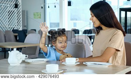 Mother With Kid Girl In Restaurant. Toddler Child With Space Buns Raises Hand With Smile Sitting By