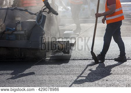 Men Working With Asphalting Paver Machine During Road Street Repairing Works At Day Light With Smoke