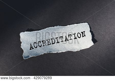 Accreditation - Text On Torn Paper On Dark Desk In Sunlight.