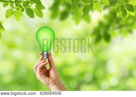 Green Idea Concept : Hand Holding Light Bulb With Blurry Green Natural In Background.