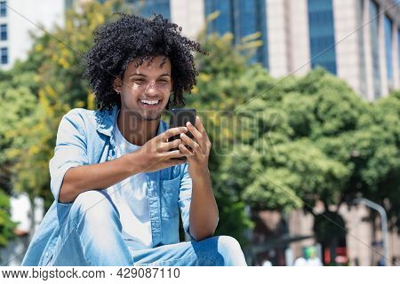 Latin American Young Adult Man Watching Video Clip With Mobile Phone Outdoor In City In Summer