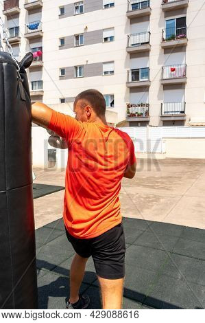 Street Fighter In Black Clothes And Bandages On The Wrist Boxing In Punching Bag Outdoors. Young Man