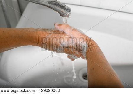 Top View Close-up Senior Woman Washes Wrinkled Hands With Soap, Disinfects From Bacteria And Viruses