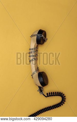 Telephone Receiver Wrapped In A Steel Chain On A Yellow Background. Top View