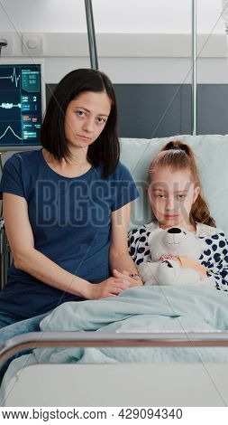 Portrait Of Worried Mother And Girl Child Looking Into Camera Durinh Illness Therapy Examination In