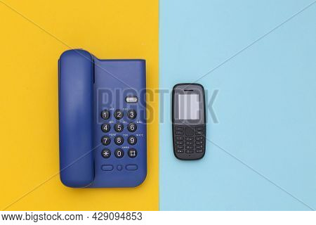 Office Landline And Push-button Telephone On A Blue-yellow Background. Top View