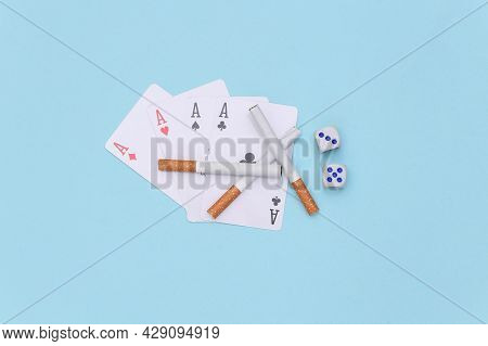 Cigarettes With Dice And Four Aces On Blue Background