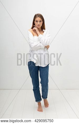 Young Attractive Caucasian Woman With Long Brown Hair In Shirt, Blue Jeans On White Studio Backgroun