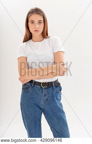 Portrait Of Young Attractive Caucasian Woman With Long Hair In T-shirt And Blue Jeans Isolated On Wh