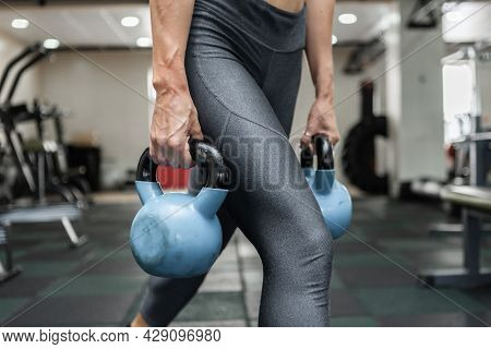 Young Muscular Woman In Sportswear Trains Lunges With A Kettlebells In The Gym. Healthy Lifestyle Co