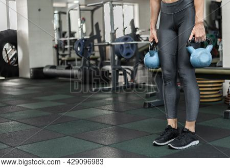 Young Muscular Woman In Sportswear Holding Kettlebells In The Gym. Healthy Lifestyle Concept. Functi