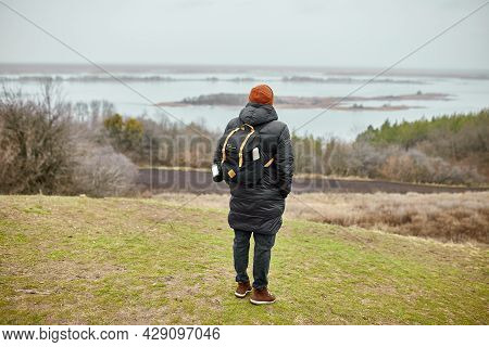 Male Hiker Travelers With Backpack Walking Along Mountains Against The River View