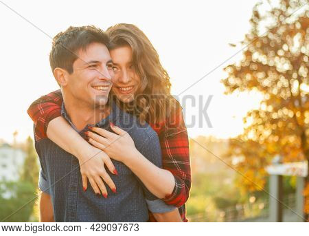 Young Couple In Love. Smiling Girl With Her Boyfriend Hugging At Sunrise In The City