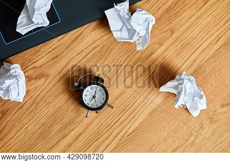 Top View Of Wooden Office Desk With Clock,, Notebook, Crumpled Paper Balls