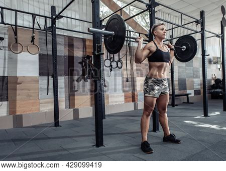 Portrait Of A Young Muscular Woman Athlete With A Barbell On Her Shoulders In A Modern Cross Gym. Sp