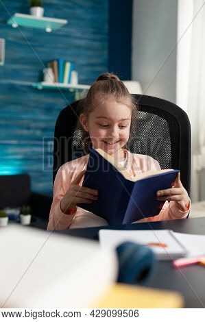 Little Caucasian Student Holding Book Reading Pages For School Work Assignment Lesson On Online Inte