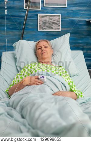 Portrait Of Disability Pensioner Senior Woman Lying In Hospital Bed Looking Into Camera During Disea