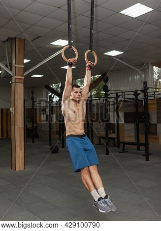 Muscular Male Gymnast Exercising On Gymnastic Rings In A Modern Health Club. Healthy Lifestyle Conce