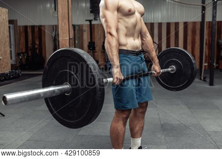 Muscular Bodybuilding Man Doing Deadlift Exercise With A Heavy Barbell In A Modern Health Club. Body