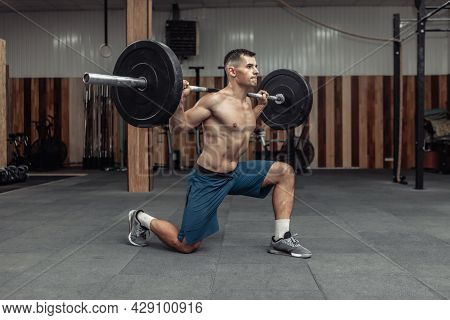 Young Muscular Male Bodybuilder Doing Lunges With A Barbell On His Shoulders In A Modern Health Club