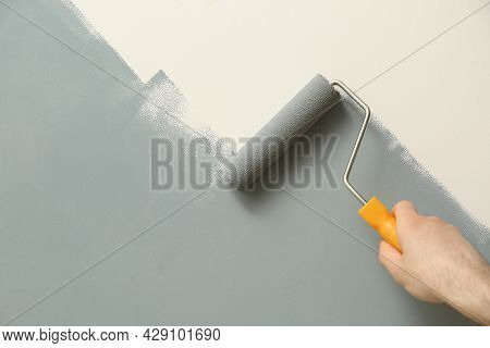 Man Applying Grey Paint With Roller Brush On White Wall, Closeup