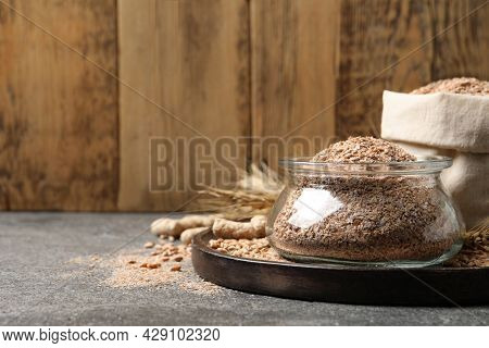 Jar Of Wheat Bran On Grey Table, Space For Text