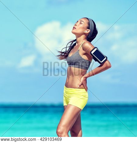 Tired athlete running woman taking a break during run breathing exhausted on hot summer day having heat stroke. Asian runner listening to music with wireless earbuds on mobile phone app.