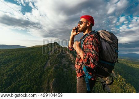 A Male Traveler In A Red Hat With A Backpack Is Talking On The Phone Against The Background Of Mount