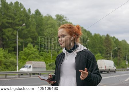 Teenager On The Street. The Girl Is Waiting For The Bus.