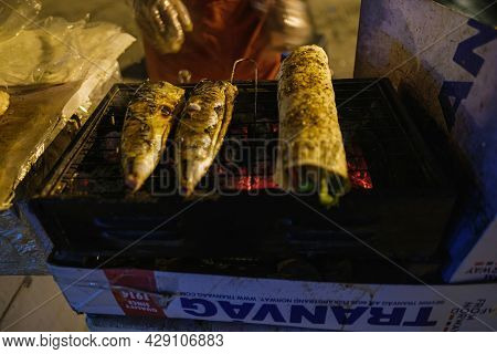 Beyoglu, Istanbul, Turkey - 07.07.2021: Fried Fishes And Hand Of A Vendor Frying Fish On Portable Ma