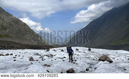 Tourists Walk Along The Miley Glacier. Mountain Landscape Of North Ossetia. Climbing Kazbek From The